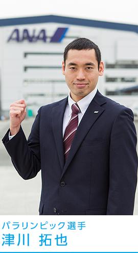 パラリンピック選手、津川拓也がANAの会社の前でガッツポーズをしている画像