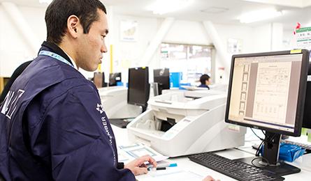 津川選手が会社でパソコンの前にて作業している画像